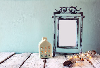 old victorian steel blue blank frame next to log tree with fairy christmas lights and house lantern on wooden table