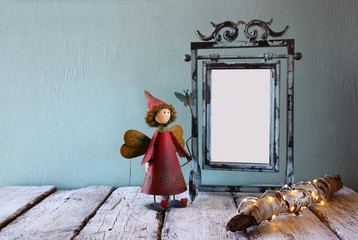 low key image of old victorian steel blue blank frame, tree log with fairy lights and cute fairy on wooden table