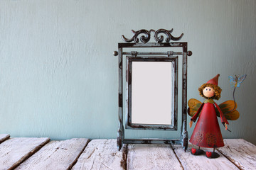 low key image of old victorian steel blue blank frame and cute fairy on wooden table