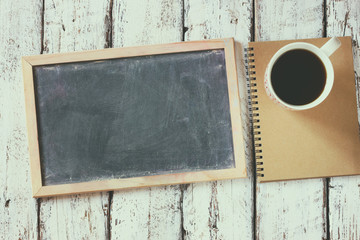 top view image of empty blackboard next to cup of coffee and notebook, over wooden table