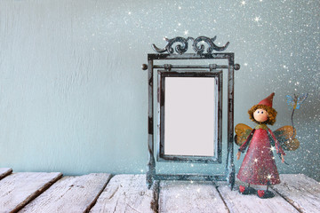 low key image of old victorian steel blue blank frame and cute fairy on wooden table. glitter overlay
