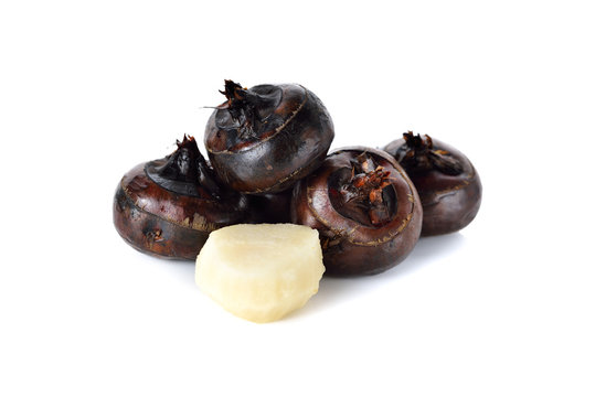 whole and peeled Chinese water chestnut or waternut on white bac