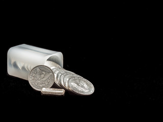 Modern and antique silver dollars spilling out of a  Treasury coin holder onto a black background with a one troy ounce silver bar.