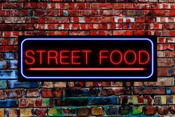Street Food Neon sign on a Graffiti. Bricks wall