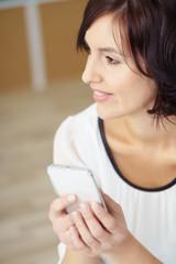 attraktive frau hält smartphone in der hand