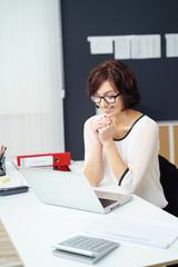 lächelnde mitarbeiterin sitzt am schreibtisch und schaut auf ihren laptop