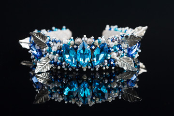 diadem with large blue stones. bijouterie. on black background