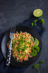 couscous with  vegetables and parsley on black plate
