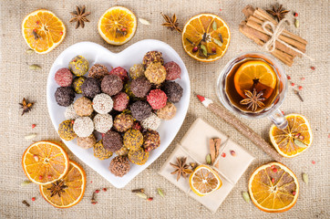 Handmade chocolate candies collection, dried oranges, spices, mulled wine, wooden pencil on wooden background. Christmas, New Year and winter.