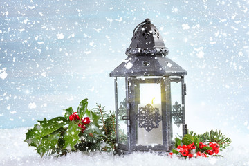 Christmas lantern with Holly leaves and berries on a snowy backg
