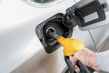 Hand holding fuel pump nozzle and refilling car