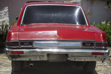 Rear view of retro old red car with sun reflections in the bumpers and the headlights. Venezuela 2015