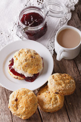 Homemade buns with jam and tea with milk close-up. Vertical