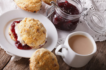 Homemade scones with jam and tea with milk close-up. horizontal