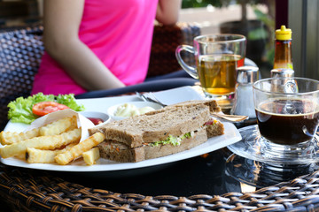 Tuna sandwich on plate and chips ,coffee , tea with woman on the