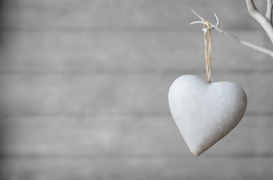 White Heart Hanging from Tree on Wood Background