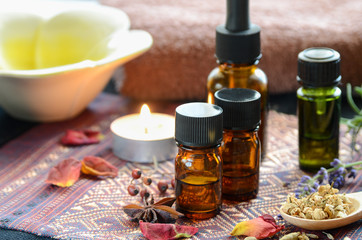 essential oils with herbs and candle for aromatherapy treatment