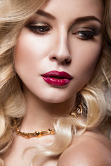 Beautiful blonde in a Hollywood manner with curls, red lips. Beauty face