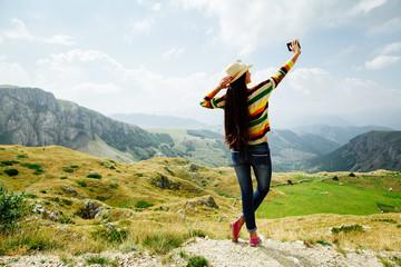 selfie photo long hair girl taking on smartphone in  mountain vi
