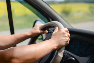 Man's hands gripping wheel of car