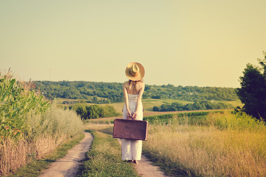 Backview of exciting young woman with suitcase standing on country road