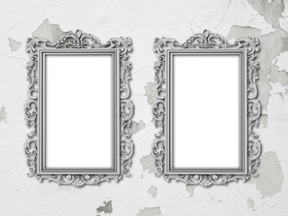 Two silver baroque frames on grey scratched and cracked concrete wall background