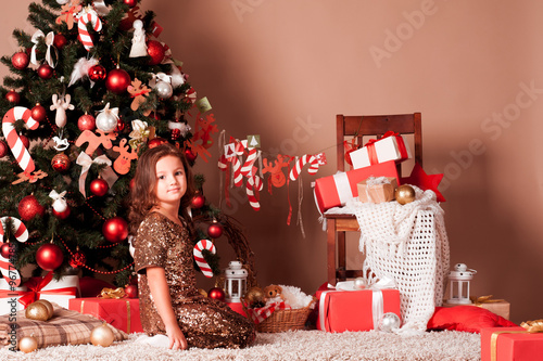 pretty child girl 5 6 year old sitting under christmas tree in room looking - Holiday Time Christmas Decorations