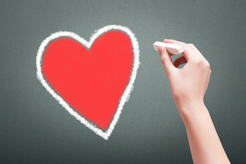 Hand holding white chalk drawing heart