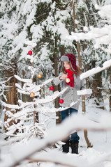 young girl dressed in red scarf and hat outdoors in a snowy forest decorating a tree for Christmas