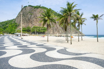 Scenic karst mountain landscape with iconic sidewalk tile pattern at the Leme end of Copacabana Beach in Rio de Janeiro, Brazil