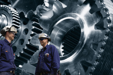 Wall Mural - two industry workers with a giant cogwheels and gears machinery powered by chains