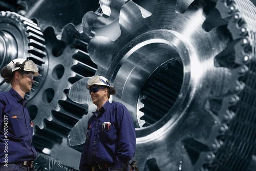Wall mural two industry workers with a giant cogwheels and gears machinery powered by chains