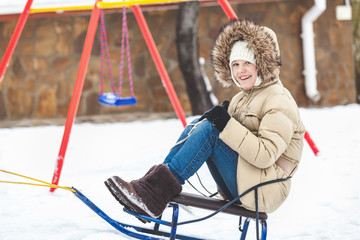 young girl rides on sled in winter