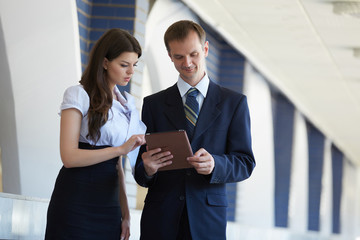 business woman and a businessman with a tablet