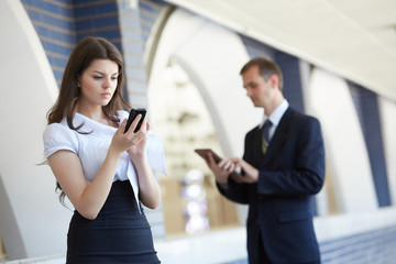 business woman with a telephone and a businessman with a tablet