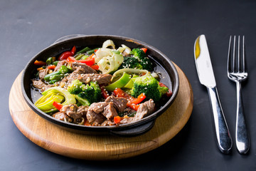 beef stew with vegetables in a frying pan over dark background
