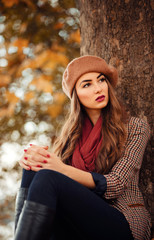 slender young brunette beautiful girl with long hair in a beret with a scarf and coat walks in autumn park with a lot of yellow and orange leaves
