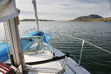 Prow view of sailboat sailing across Alange Reservoir, Spain