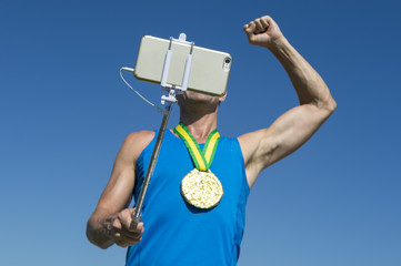 Gold medal athlete punching the air for a selfie with a mobile phone on a selfie stick