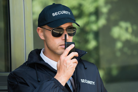 Young Security Guard Talking On Walkie-talkie
