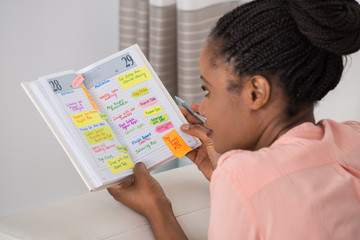 Fototapete - Young Woman Writing Schedule In Diary