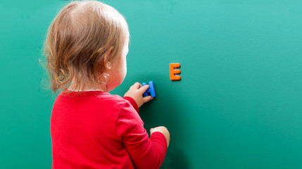 Toddler girl learning her ABCs on a chalkboard