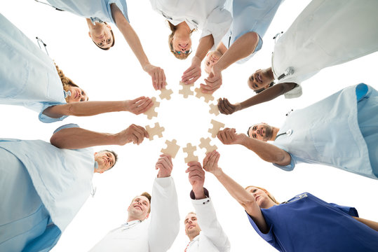 Medical Team Joining Jigsaw Pieces In Huddle
