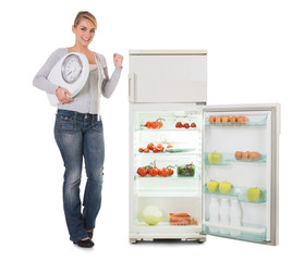 Woman Holding Weighing Scale While Standing By Refrigerator