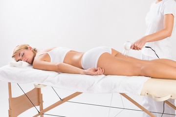 Beautician Using Cellulite Vacuum On Woman's Thigh