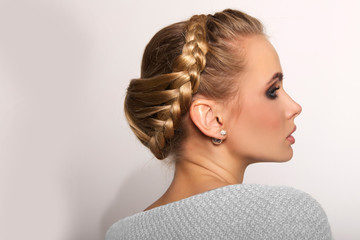 portrait of a beautiful young blonde woman on a light background with hairdo on her head. copy space.