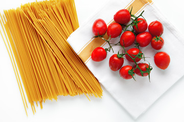 cherry tomatoes and spaghetti pasta on a towel