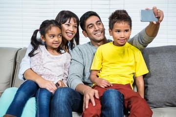 Happy family taking selfie on sofa