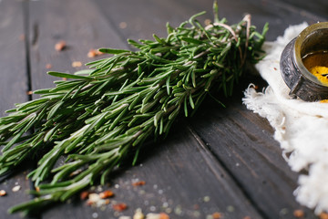 Rosemary on a black wooden background with a free space