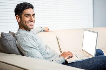 Handsome man using laptop on sofa